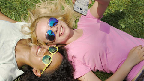 Pretty multiracial girls taking selfie on smartphone, relaxing on lawn in park Footage