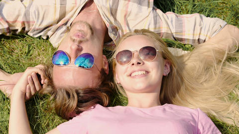 Happy young couple enjoying weekend, lying on lawn and talking, summertime Footage