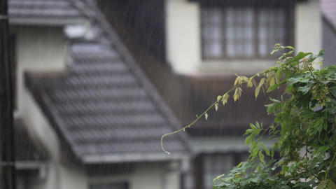 Summer rain falling on rural houses, raindrops flowing down along roof Footage
