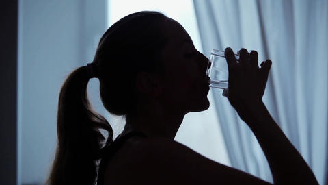 Woman drinks a glass of water