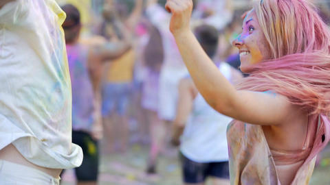 Energetic young couple covered in coloured powder dancing to music and smiling Footage