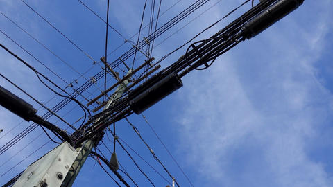 A slow pan of a utility pole loaded with cables Footage