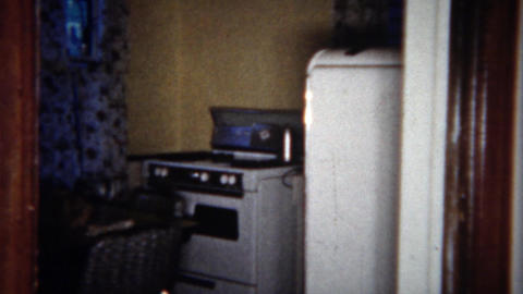1963: Modest middle class retro lifestyle kitchen table stove and refrigerator.  Footage