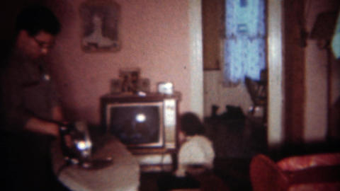 1963: Dad irons clothes in living room while daughter sits inches from TV. BUFFA Footage