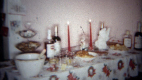 1962: Holiday party table filled with self serve desserts and liquor bottles. BU Footage