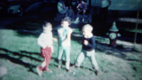 1961: Toddler kids practice twist style dancing craze in sunny front yard. CINCI Footage