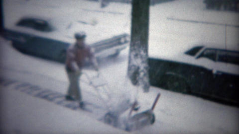 1967: Man using snowblower machine after winter storm on urban sidewalk. BUFFALO Footage