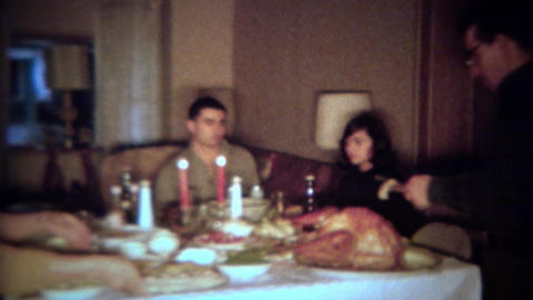 1964: Father carving turkey for intimate holiday candlelight dinner feast. PLANO Live Action