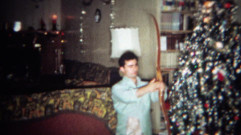 1966: Man gets wooden archery recurve bow and arrows for Christmas gift. BUFFALO Footage