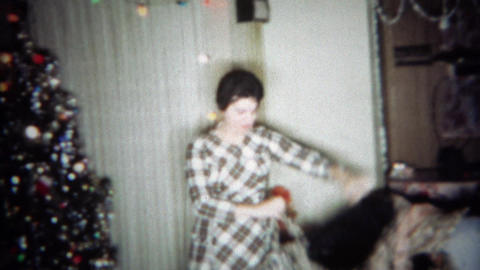 1966: Women gets fur coat gift for Christmas models in front of tree. BUFFALO, N Footage