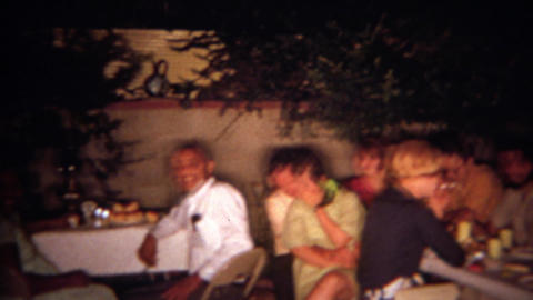 1966: Adult tiki torch tropical Hawaiian theme night time backyard party. SAN DI Footage