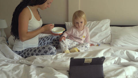 Young pretty woman feeding little baby girl porridge while looking on tablet com Footage