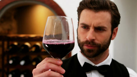 Waiter looking at glass of red wine at counter Live Action