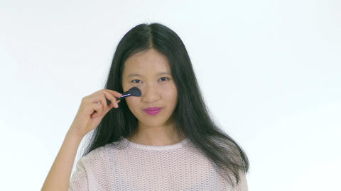Chinese teenager applying makeup with brush and smiling 1 Filmmaterial