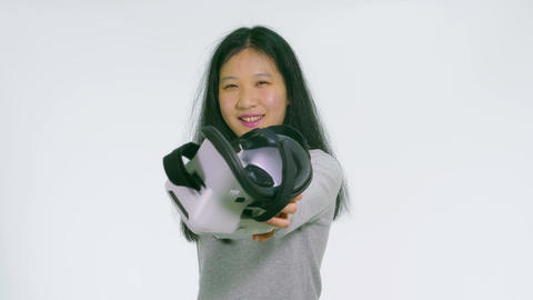 Teenage Asian girl takes off and hands over VR goggles 1 Filmmaterial