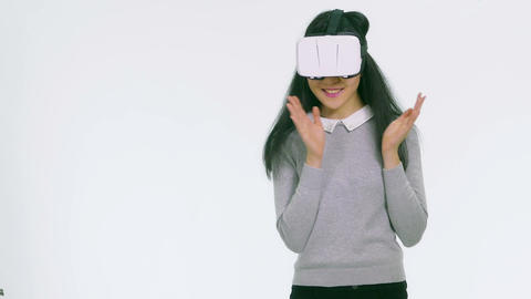 Teenage Asian girl wearing VR goggles dancing and clapping 1 Filmmaterial