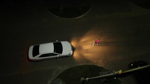 Wideshot Top View Car Headlight to Illuminate Child on Bicycle Footage