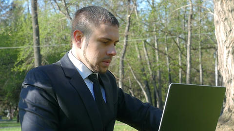 Serious businessman co-working outdoor with laptop Footage