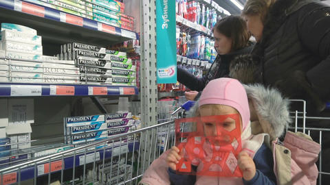 Little boring girl is waiting while parents are shopping Footage