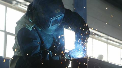 Welder Works Hard in Sparks Shower Clouseup Footage