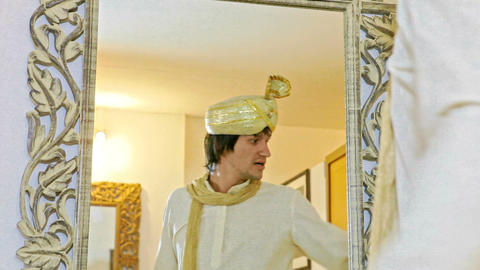 Groom Looks at Himself in Traditional Dress in Mirror Footage