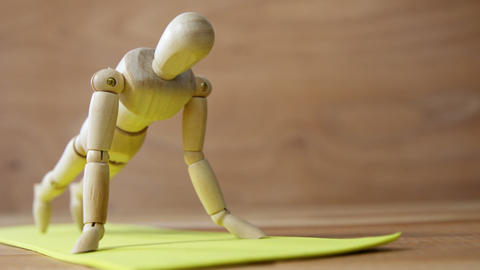 Wooden figurine exercising push up on exercise mat against wooden background Live Action
