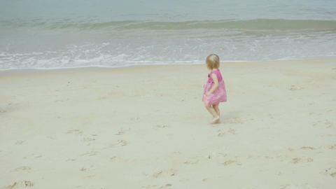 Little cute girl walking along coastline Footage