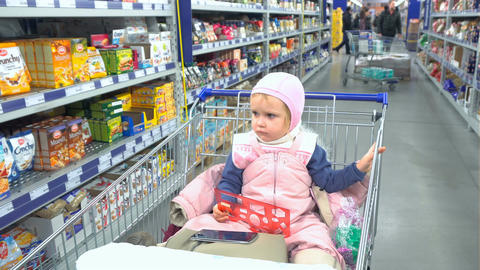 Bored child waiting for the parents in supermarket Footage