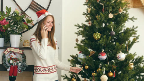 Pretty girl talking on the phone nearby Christmas tree Footage