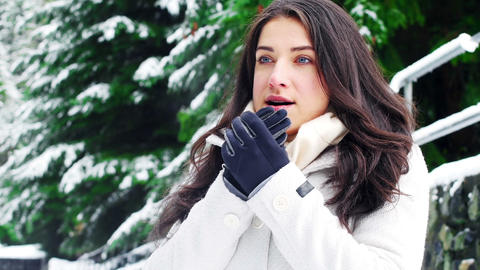 Woman in warm clothing warming her hands Live Action