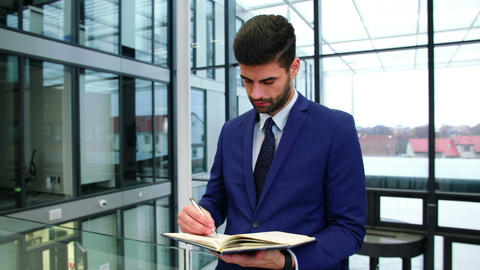 Businessman writing in diary at office Live Action