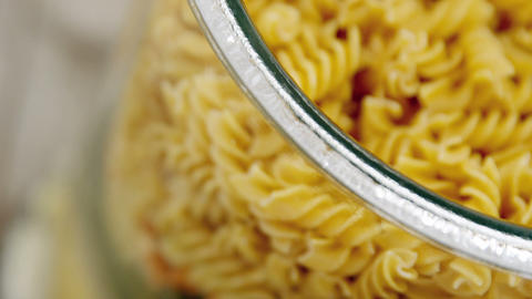 Close-up of colored and original Fusilli pasta in transparent jar glass Live Action