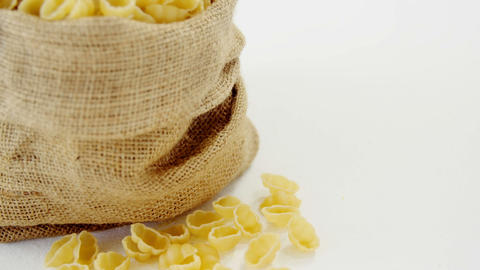 Raw gnocchi pasta in hessian sack on white background Footage
