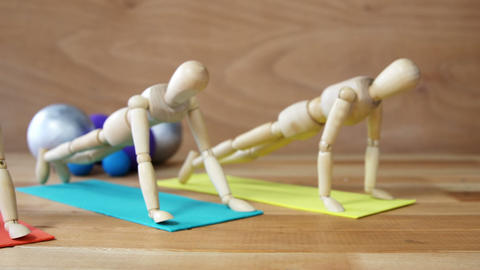 Wooden figurines exercising push-ups on colored exercise mat in front of gym balls against wooden ba Live Action