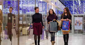 Female friends walk at shopping mall with sale bags HD video. Women shoppers Footage