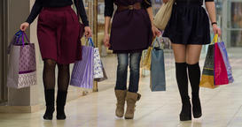 Female friends walk at shopping mall with sale bags HD video. Young shoppers Footage
