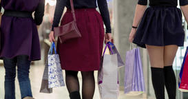 Female shoppers walk at shopping mall with sale bags HD video. Back view Footage