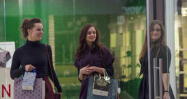 Female shoppers walk at shopping mall with sale bags HD video. Girl buyers Footage