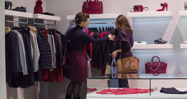 Two women shopping at clothing store HD video. Girls looking outerwear on hanger Footage