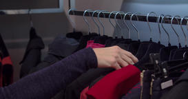 Women shopping at clothing store HD video. Hand looks for outerwear, hangers Footage