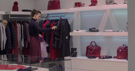 Woman shopping at clothing store HD video. Girl looks wear rack in boutique Footage