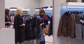 Women shopping at clothing store HD video. Female friends choose wear boutique Footage