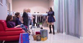 Female shopping at clothing store HD video. Woman trying on dress fitting room Footage