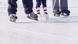 Close-up family legs slides on ice skates kid training HD video. Children foots Footage