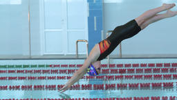 Female swimmer jumps off starting block start swims in pool HD slow-motion video Footage