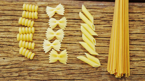 Various pasta on wooden table background Footage