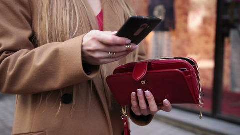Elegant woman's hand opening red purse outdoors Footage