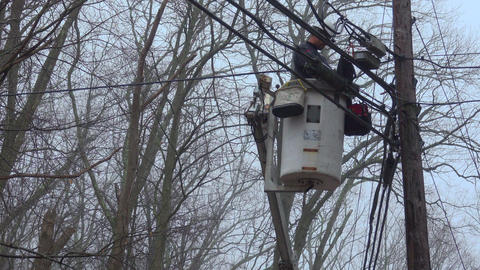Utility worker works from a bucket near powerlines Footage