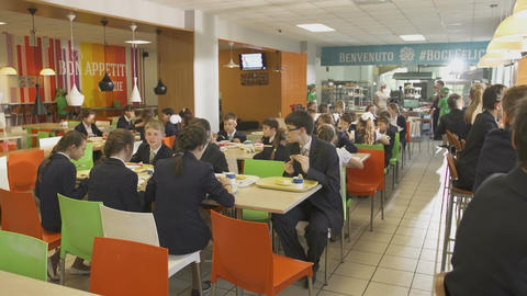 Pupils in School Uniform Sit at Tables with Lunch Footage