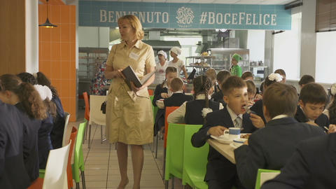 Teacher in White Dress with Magazine Walks between Tables Live Action